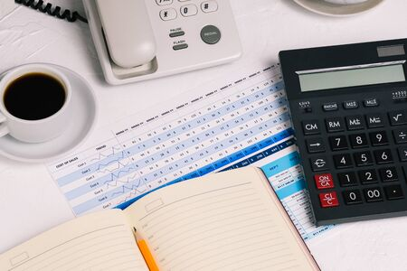 Workplace of a company employee with a calculator, a daily planner, a Cup of coffee and financial documents. Tables with graphs. Business concept, banking and accounting Foto de archivo