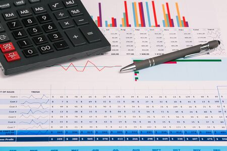 Calculator and pen on charts and tables. Business concept, financial papers and accounting