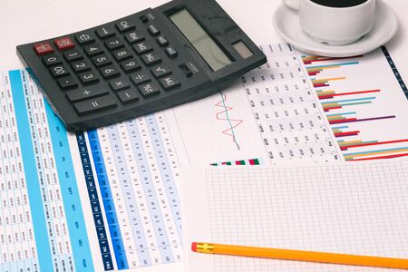 A table with the company's financial indicators, a calculator, a Cup of coffee, and a Notepad with a copy of the space. Earnings and income of the enterprise. Office Desk of an accountant, analyst.