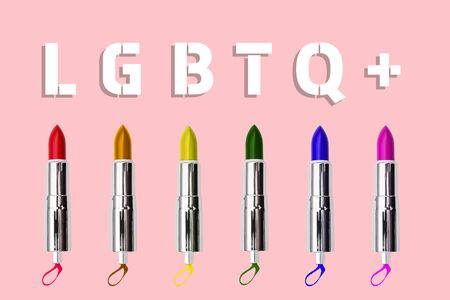 Multi-colored women's lipstick on a pink background. Rainbow colors and text of the LGBTQ community. Creative minimal style. LGBT concept