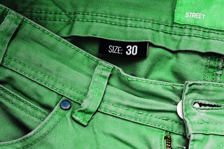 Green jeans in size forty. Jeans pocket and denim background. Men's or women's trousers close-up. Street fashion clothing. Denim fashion.