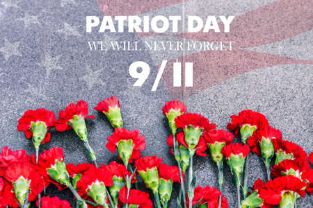Carnations on the memorial with the American flag and the phrase patriots  Day. September 11. We will never forget. Anniversary of the attack.