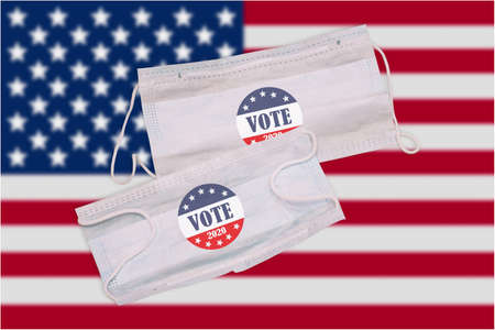 Medical masks on the background of the American flag with a vote button. Presidential elections 2020 in the United States of America. Protection from coronavirus