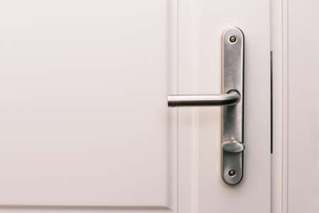 White door and handle. Entrance to an apartment, office, or bedroom. Door detail. Interior of a house or hotel.