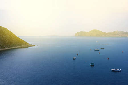 Mountains by the sea in the sun. Seascape with mountains and boats. Adventure and travel concept