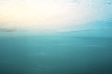 Seascape with a wide horizon of sky and sea. Skyline. The turquoise surface of the sea or ocean. Sunrise or sunset over the sea