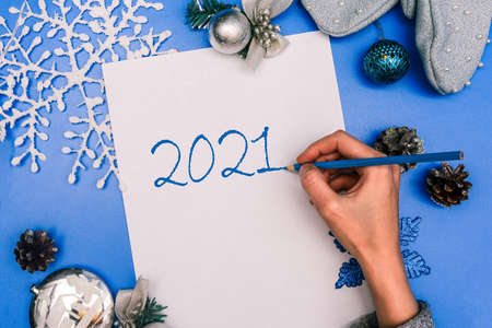 The female hand writes 2021. Christmas composition with a sheet of paper, mittens, a Christmas tree toy and a garland. Christmas background