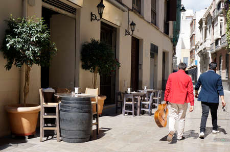 busker: Street in Malaga with bar tables, chairs and street musicians