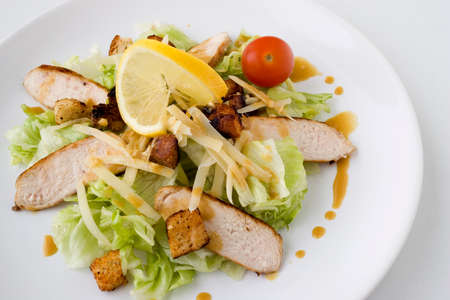 A Caesar Salad with shredded parmesan cheese, croutons and chicken  photo