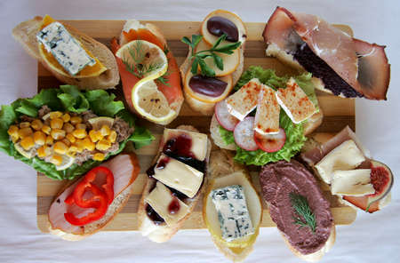 Variety of fresh canapes on a cutting board photo
