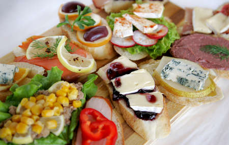 Fresh canapes on a wooden board photo
