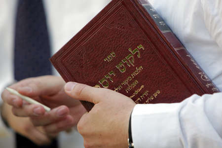 A jewish prayer holds holy book and wooden pencil in his hands  photo
