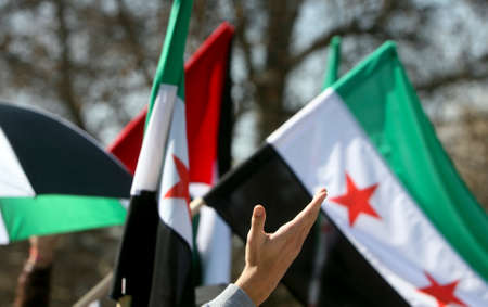 arab spring: Human hand waving in front of Syrian flags  Stock Photo