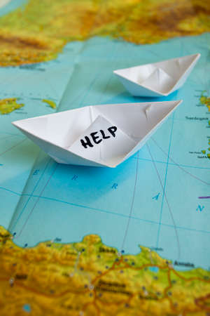 paper boat: White paper boat onto world map with Help sign on it.