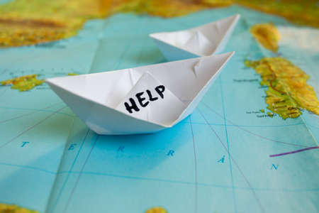 migrations: White paper boat onto world map with Help sign on it.
