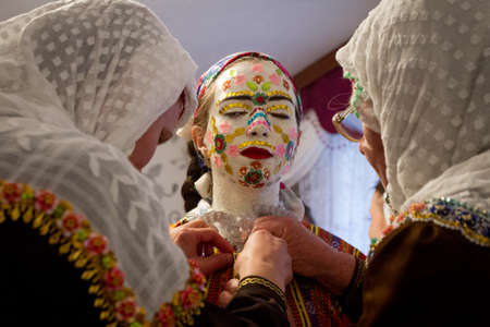 grannies: RIBNOVO, BULGARIA - FEBRUARY 15: Bulgarian Muslims grannies give a final preparation for Fikrie Bindzheva wedding costume and special sacred mask during wedding ceremony, Feb 15, 2015, Ribnovo, Bulgaria.