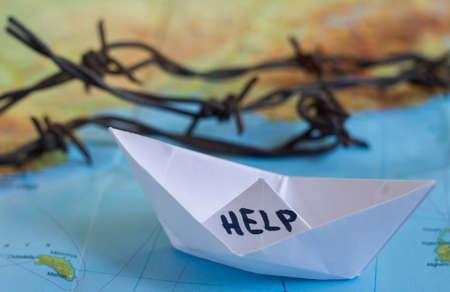 """bateau: Livre blanc bateau sur la carte du monde avec """"Aide"""" signe sur elle et de barbel�s."""