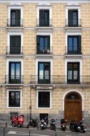 mediterraneo: Building facade and parked motorbikes in central Madrid, Spain. Stock Photo