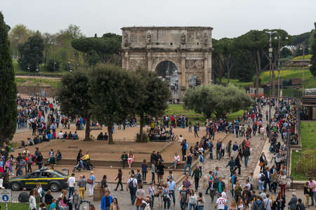 ROME, ITALY - APRIL 7: Tourists visiting Arco de Constantino (Arch of Constantine) and Colosseum. The arch was erected by the Roman Senate to commemorate Constantine victory over Maxentius