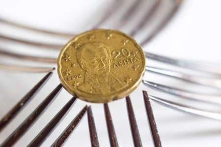 five cents: 20 euro cents seen over five silver forks. Stock Photo