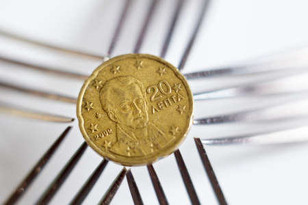 displeasure: 20 euro cents seen over five silver forks. Stock Photo