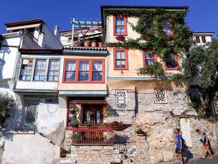 KAVALA, GRIEKENLAND - JULI 6, 2017: De toeristen gaan langs kleurrijke huizen in de oude stad van Kavala over.