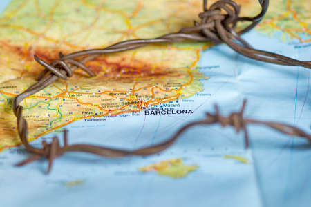 Barbed wire seen over Barcelona town map.