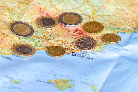 Spainish Euro coins are seen over map of Catalonia region in Spain.