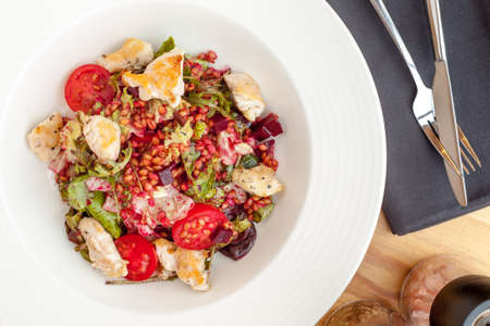 Hot chicken salad with einkorn, salad mix, red beetroot and cherry tomatoes. Zdjęcie Seryjne