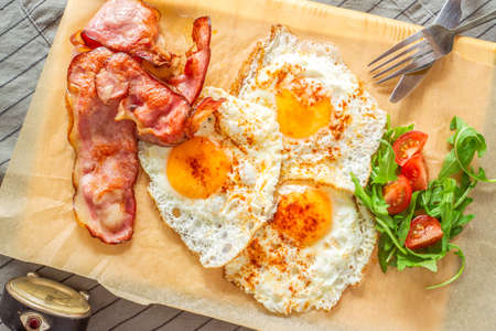 English breakfast with ham and eggs served on a wooden plate.