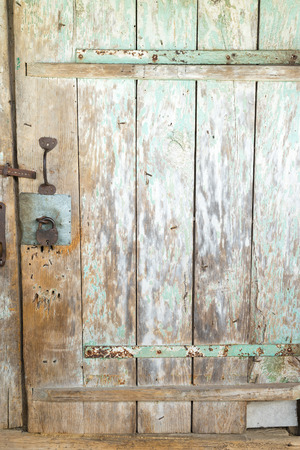 hinges: Wooden door with metal hinges with pieces of old green paint. Stock Photo