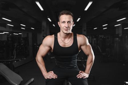 Fitness strength training workout bodybuilding concept background - muscular bodybuilder handsome man doing exercises in gym naked torso Banque d'images