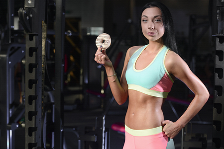 Fitness strength training workout bodybuilding concept background - woman in gym holding donut, doughnut