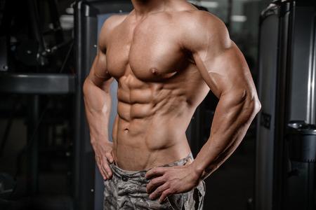 Starker und stattlicher athletischer junger Mann mit Muskeln abs und Bizeps. Nahaufnahme eines Strom Fitness Mann Standard-Bild - 67762660