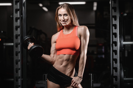 Athletic young woman posing and exercising fitness workout with weights in the gym lifestyle portrait, caucasian model