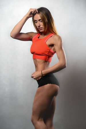 beautiful young athletic fitness model girl posing in studio on a white or grey background Stock Photo