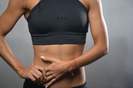 Schöne junge athletische Fitness-Modell Mädchen posiert im Studio auf einem weißen oder grauen Hintergrund Standard-Bild - 71628925