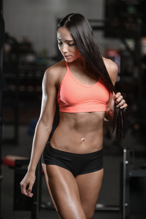 Athletic young sexy fitness woman train and exercising in gym healthy living caucasian brunette girl diet in joy posing