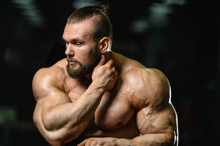 lose up: Portrait of a handsome guy on a background of gym. Face of brutal muscular sexy men in fitness gym