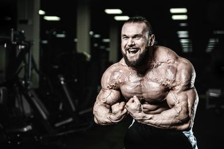 Handsome fit caucasian muscular man flexing his muscles in gym on diet. Brutal bodybuilder powerful training and execute exercise Stock Photo
