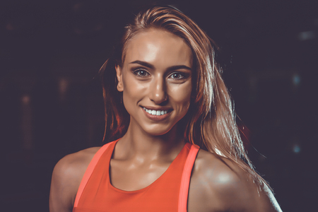portrait of a beautiful sexy girl on a background of a gym. face of gorgeous blonde girl with long dark curly hair