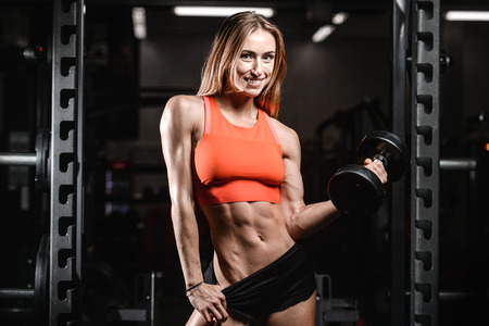 Caucasian pretty fitness girl on diet training pumping up muscles with dumbbell and barbell in gym