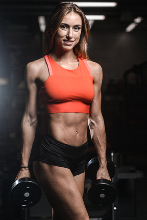 execute: Caucasian pretty fitness girl on diet training pumping up muscles with dumbbell and barbell in gym