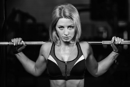 lose up: Sexy pretty caucasian fitness model on diet resting and working out in the gym. Girl execute exercise with barbell Stock Photo