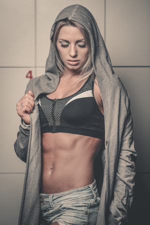 Pretty fitness girl in locker room in gym. Young sexy woman on diet dress up in changing room Imagens