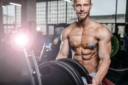 lose up: Brutal bodybuilder on diet resting and working out in the gym. Caucasian sexy fitness male model execute exercise with barbell