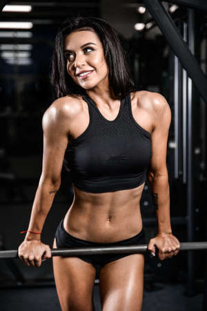 Sexy pretty caucasian fitness model on diet resting and working out in the gym. Girl execute exercise with barbell Stock Photo