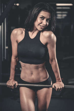execute: Sexy pretty caucasian fitness model on diet resting and working out in the gym. Girl execute exercise with barbell Stock Photo