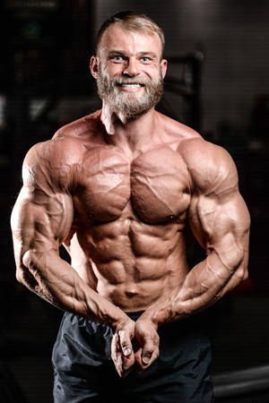 execute: Handsome fit caucasian muscular man flexing his muscles in gym on diet. Brutal bodybuilder powerful training and execute exercise Stock Photo