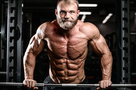execute: Brutal bodybuilder on diet resting and working out in the gym. Caucasian sexy fitness male model execute exercise with barbell